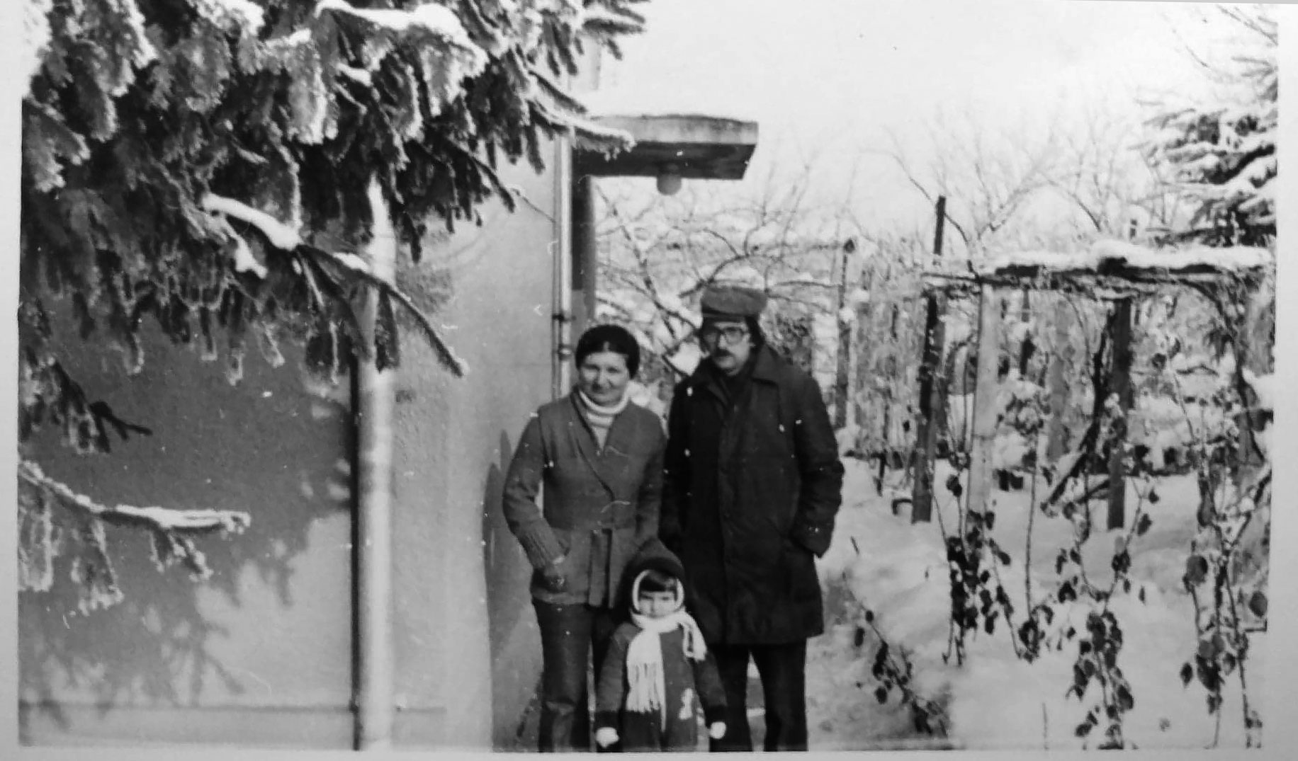 black and white image of three people in front of a building. lots of snow on the ground and on the tree branches.