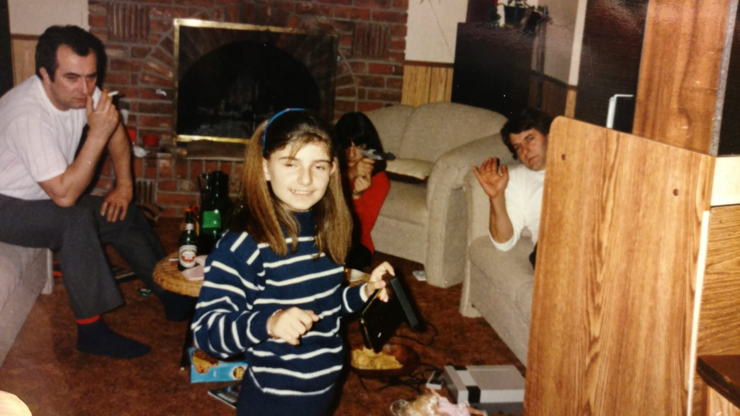 This is the only photo I have that captures this moment. You can see my cousin Eva in the background shooting. My uncle is smoking on the left and that's my dad waving on the right. I'm in front with my crimped hair and goofy look.